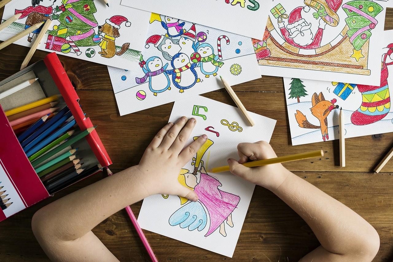 机の上で絵を描く小学生