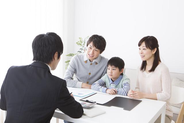 先生の話を真剣に聞く家族と小学生
