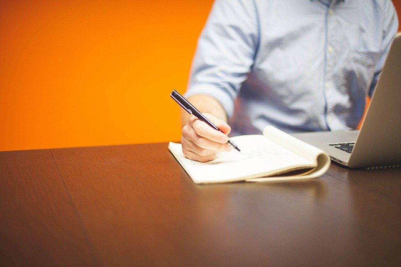 ノートに英文を書き取る男性