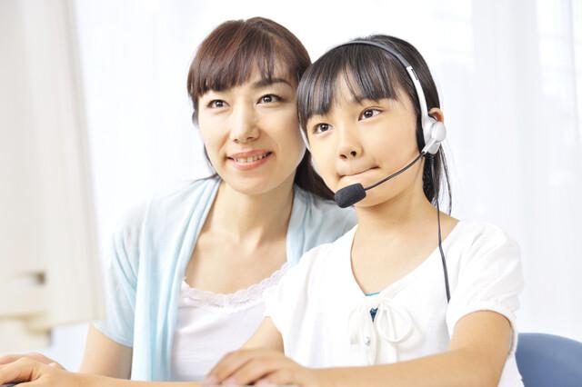 ICT機器を利用する子どもとそれを見守る母