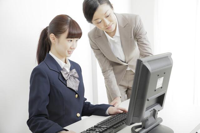 PC画面を使って説明するスタッフとそれを聞く学生